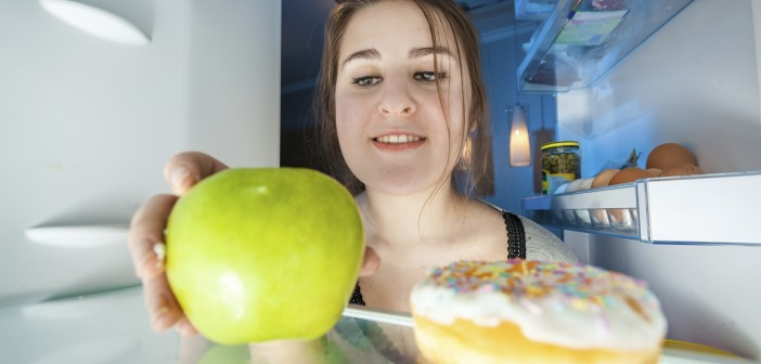 Portrait from inside the fridge of woman taking apple