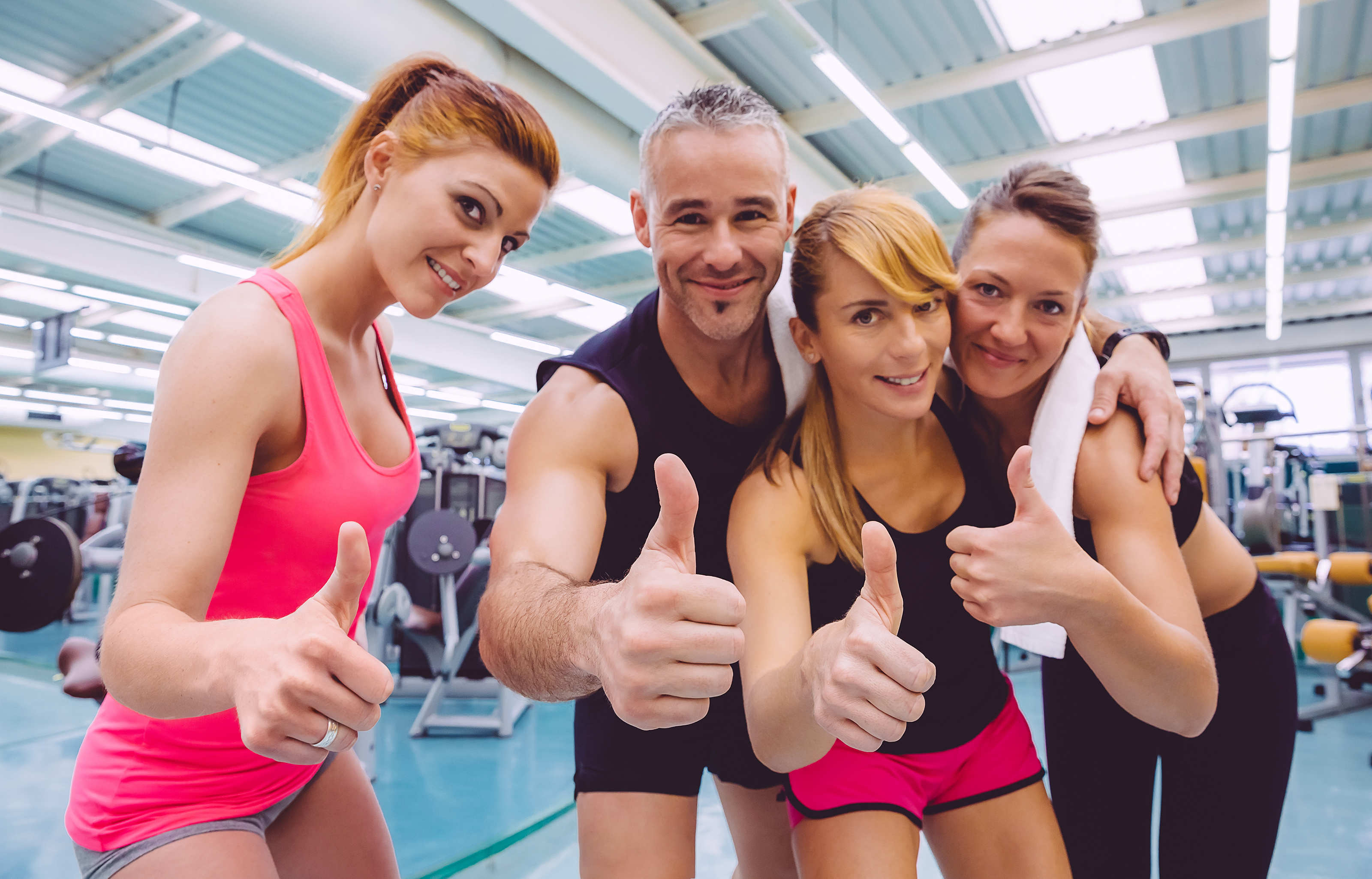 Group of friends with thumbs up smiling on a fitness center after hard training day. Selective focus on hands.