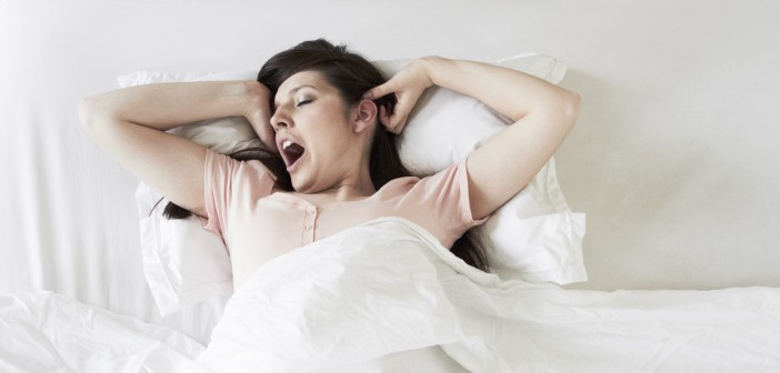 Woman waking and yawning in bed